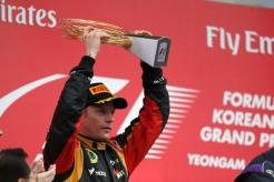Kimi Raikkonen, Lotus F1, 2nd position, lifts his trophy on the podium.
